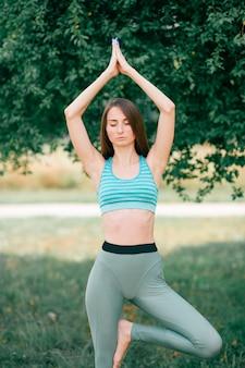 Brünettes fitnessmädchen, das yogain sommerpark tut.
