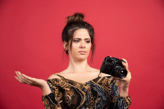 Brünettes fotomädchen überprüft ihre fotos in die kamera und sieht unzufrieden aus.