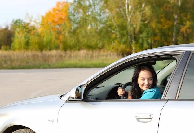 Brünettes junges mädchen, das ein auto fährt