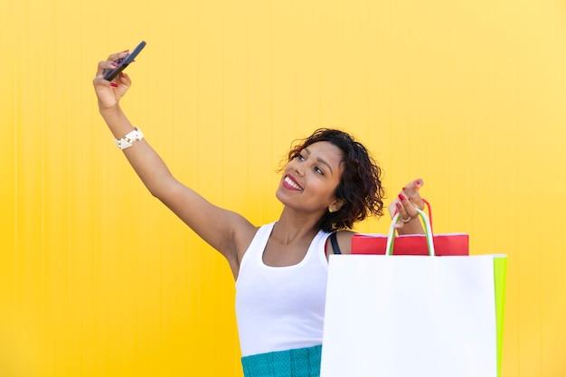 Brünettes mädchen, das ein glückliches selfie mit ihren einkaufstaschen auf einer gelben wand nimmt