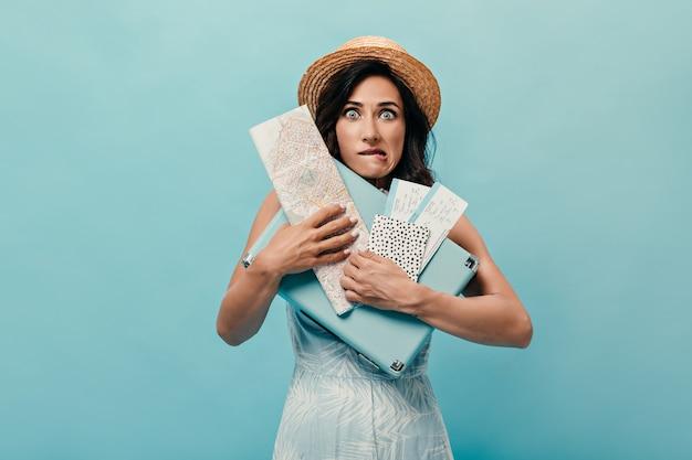 Brünettes mädchen fühlt sich unbehaglich und posiert mit koffer, tickets auf blauem hintergrund. frau im strohhut mit karte in ihren händen und im blauen kleid.