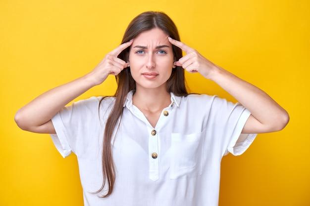 Brünettes mädchen hält gespannt die finger an den schläfen, denkt nach und trifft eine wahl isoliert auf gelbem hintergrund
