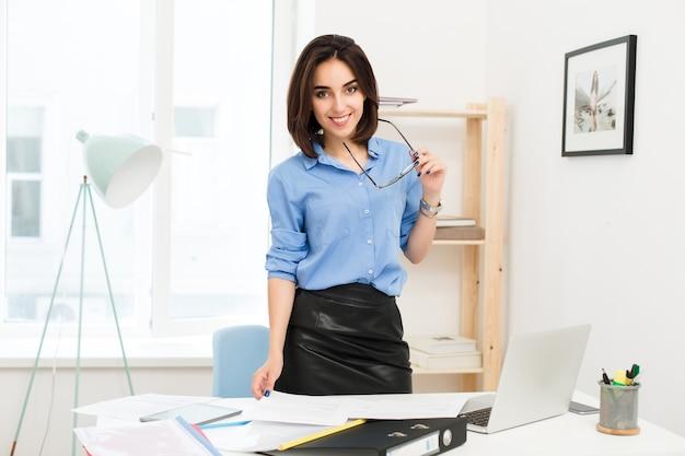 Brünettes mädchen im blauen hemd und im schwarzen rock steht nahe tisch im büro. sie hält eine brille in der hand und lächelt in die kamera.