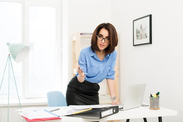 Brünettes mädchen im blauen hemd und im schwarzen rock steht nahe tisch im büro. sie legte ihre hand auf den tisch. sie schaut sehr ernst in die kamera.