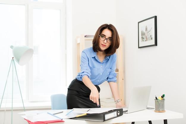 Brünettes mädchen im blauen hemd und im schwarzen rock steht nahe tisch im büro. sie legte ihre hand auf den tisch und zeigt sie den zeitungen. sie schaut ernsthaft in die kamera.