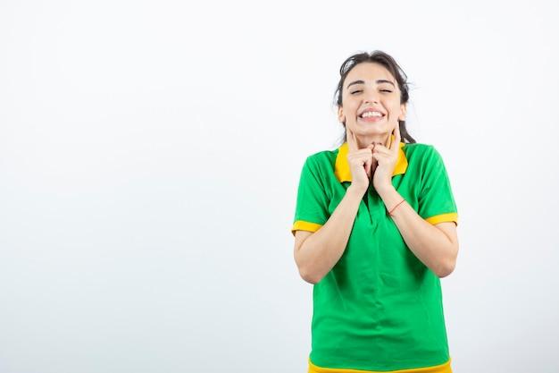 Brünettes mädchen im grünen t-shirt, das steht und sich glücklich fühlt.