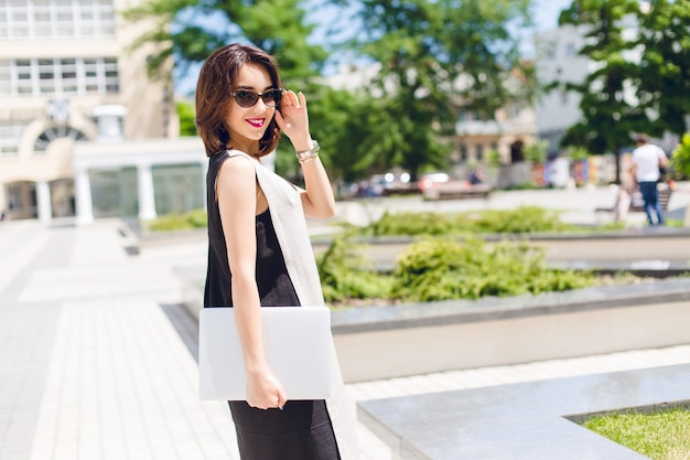Brünettes mädchen im schwarzen und grauen kleid geht im park spazieren. sie hält eine schwarze sonnenbrille im gesicht und einen laptop in der hand. sie lächelt mit weinigen lippen.
