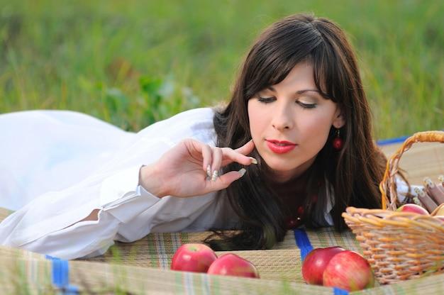 Brünettes mädchen im weißen hemd liegt auf picknickmatte nahe weidenkorb mit äpfeln