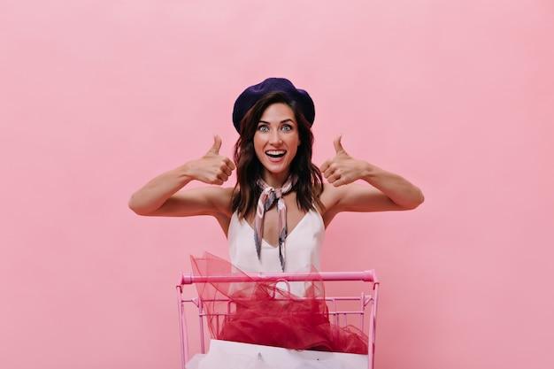 Brünettes mädchen in der blauen baskenmütze ist glücklich mit dem einkaufen und zeigt daumen hoch. glückliche frau in der guten laune im lila hut und in der weißen bluse wirft auf rosa hintergrund auf.