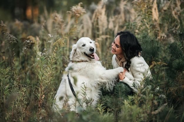Brünettes mädchen mit dem weißen goldenen retrieverhund im feld