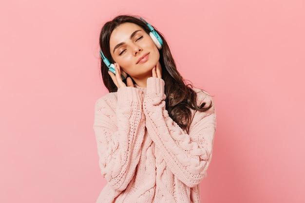 Brünettes mädchen mit vergnügen hört musik über kopfhörer. frau im rosa outfit lächelnd auf lokalisiertem hintergrund.