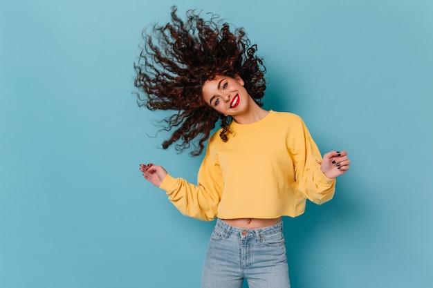 Brünettes mädchen tanzt und spielt welliges haar gegen blauen raum. porträt des niedlichen mädchens im gelben sweatshirt.