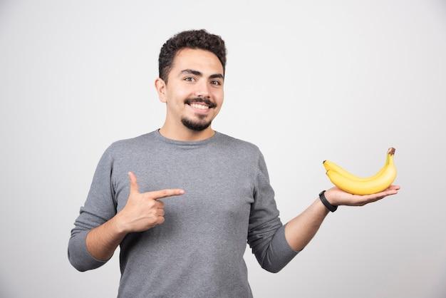 Brünettes männchen, das auf banane auf grau zeigt.