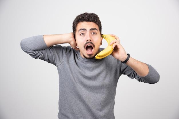 Brünettes männchen, das banane als telefon hält.