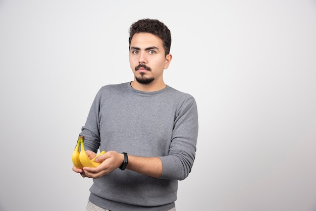 Brünettes männchen, das banane auf grau hält.