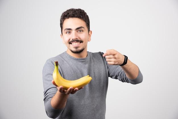Brünettes männchen, das banane hält und darauf zeigt.