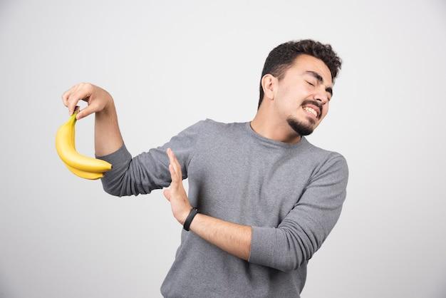 Brünettes männchen, das banane hält und daumen aufgibt.