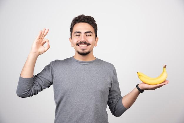 Brünettes männchen, das banane hält und ok zeichen gibt.
