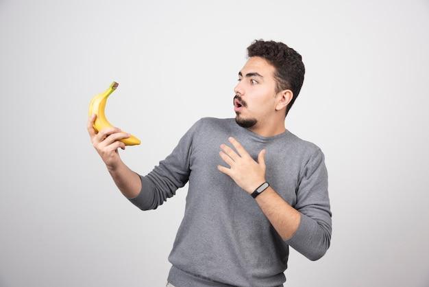 Brünettes männchen, das banane mit überraschtem ausdruck betrachtet.