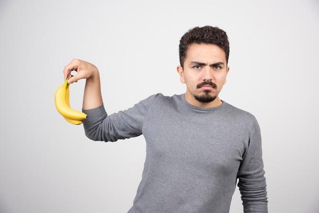 Brünettes männchen, das banane mit wütendem ausdruck hält.
