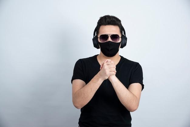 Brünettes mannmodell mit sonnenbrille, die in der medizinischen gesichtsmaske und in den kopfhörern aufwirft.