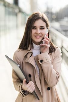Brünettes model mit laptop in den händen hat einen anruf auf ihrem handy