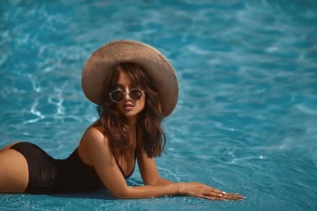 Brünettes modellmädchen mit perfektem sexy körper in einem stilvollen schwarzen bikini, glamouröser sonnenbrille und strohhut, die im schwimmbad im freien aufwerfen