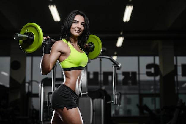 Brünettes sportliches junges mädchen, das im fitnessstudio trainiert