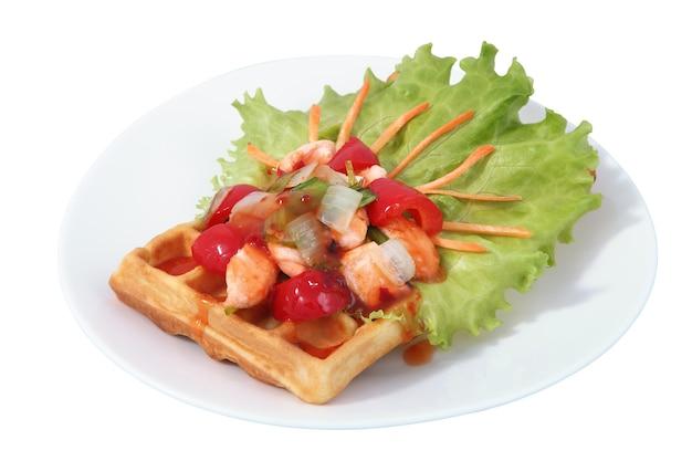 Brüsseler waffel auf teller mit salatblatt, paprika und rotem fisch, isoliertes bild auf weißem hintergrund.