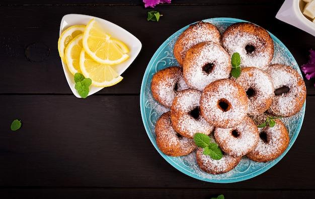 Brunch oder mittagessen. hausgemachte donuts mit puderzucker bestreut.