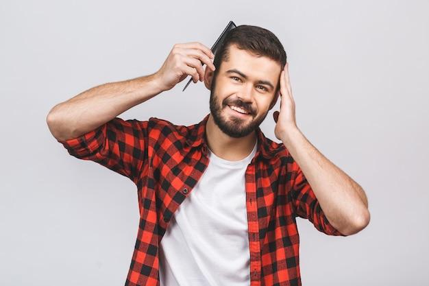 Brunet mann, der sein haar mit haarbürste kämmt, hand auf kopf hält, lokalisiert auf weißem hintergrund.