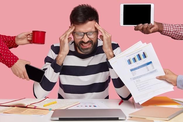 Brunet mann sitzt am schreibtisch mit gadgets und papieren umgeben