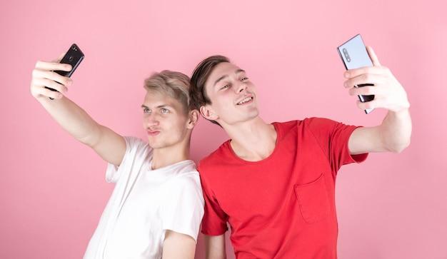 Brunet und blonde männer machen selfie mit smartphone-kamera