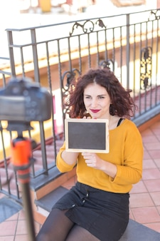 Brunette blogger, der tafel zur kamera zeigt