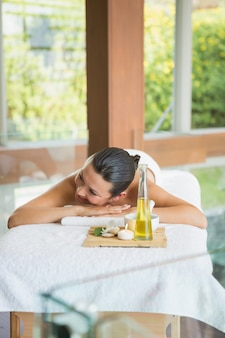 Brunette, der auf massagetabelle mit behälter von schönheitsbehandlungen liegt