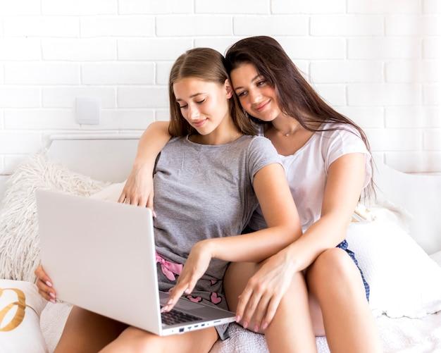 Brunette, der blondine mit einem laptop umarmt
