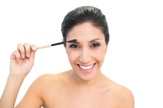 Brunette, der eine augenbrauenbürste und -c $ lächeln verwendet