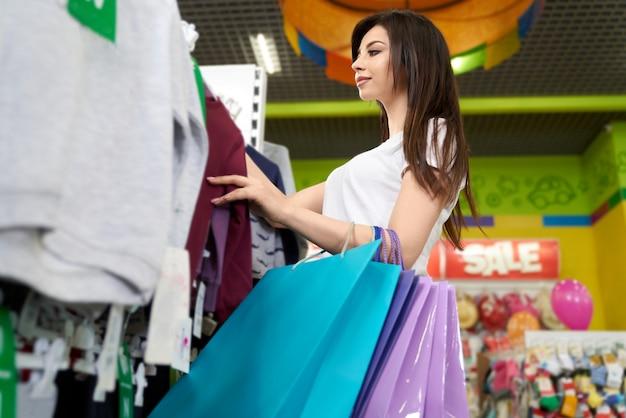 Brunette, der große papiertüten und das einkaufen hält