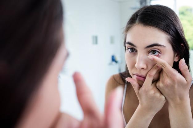 Brunette, der ihre kontaktlinse in badezimmer einsetzt