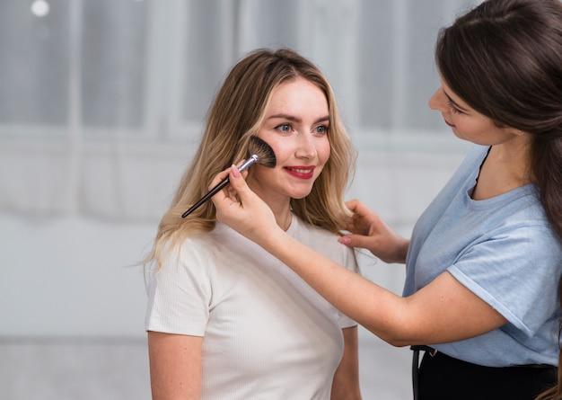 Brunette, der lächelnder frau make-up tut