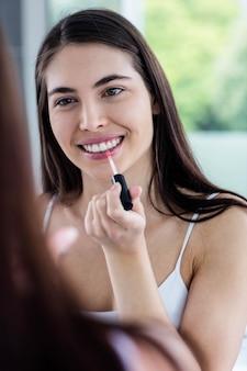 Brunette, der lipgloss im badezimmer anwendet