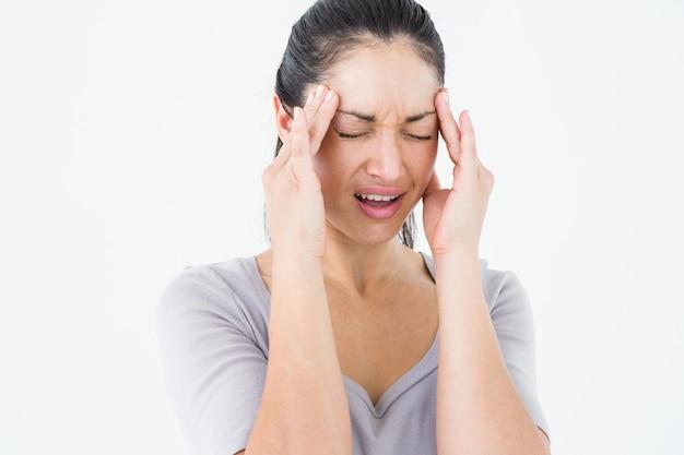 Brunette, der unter migräne auf weißem hintergrund leidet