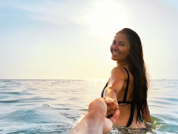 Brunette frau, die sommerbaden im meer bei sonnenuntergang genießt