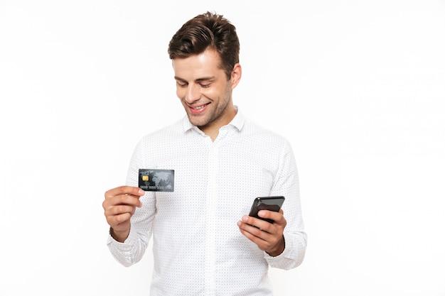 Brunette glücklicher mann mit dunklem haar, das smartphone und kreditkarte hält