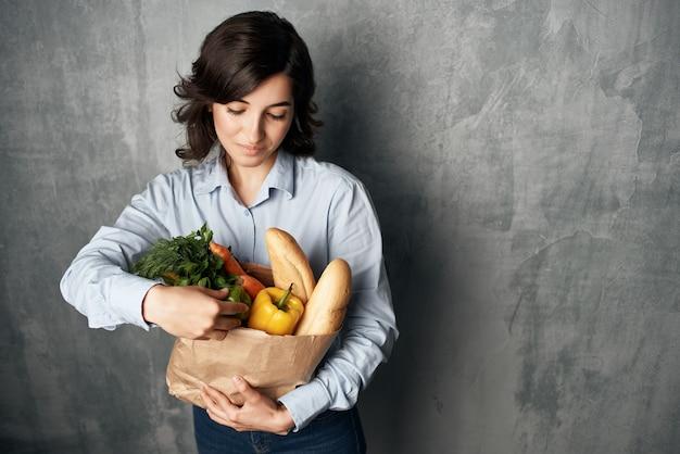 Brunette im blauen hemdnahrungsmittelpaket gesundes essen lokalisierter hintergrund