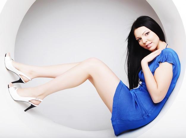 Brunette im blauen kleid, das in einem kreis sitzt