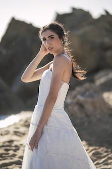 Brunette kaukasische braut, die während der hochzeit am strand aufwirft