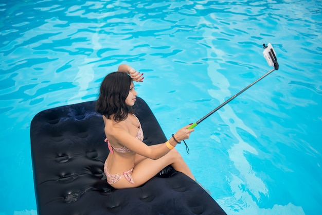 Brunette macht selfie foto am telefon mit selfie stock auf matratze im pool