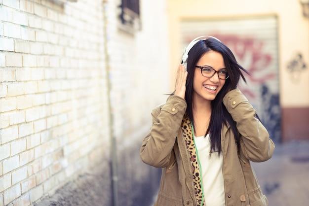 Brunette mädchen mit brille mit kopfhörer musik hören