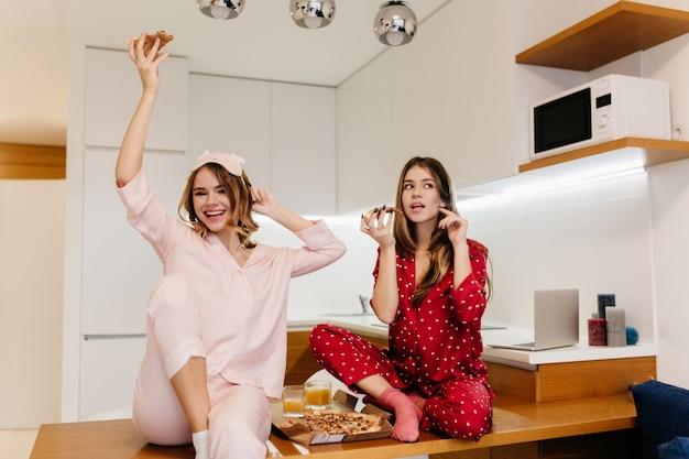Brunette mädchen sitzt auf holztisch und genießt frühstück mit saft. innenfoto der romantischen blonden frau im pyjama, die pizza in der küche isst.